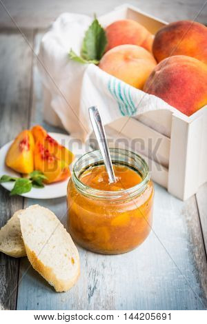 A jar with homemade peach jam in front of a white wood crate full of ripe peaches over a light blue old wood background.