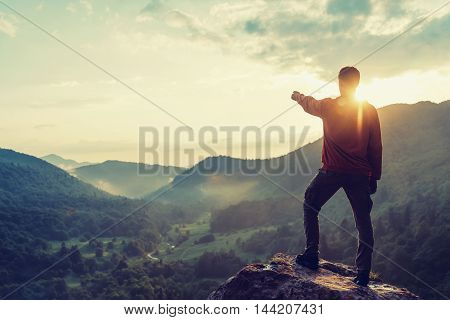 Young man pointing at something in the distance in summer mountains at sunset. Toned image