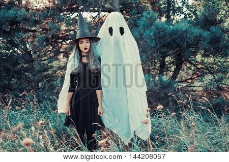 Cute Halloween couple: ghost with young witch walking in autumn forest. Toned image