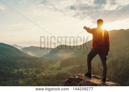 Young man pointing at something in the distance in summer mountains at sunset