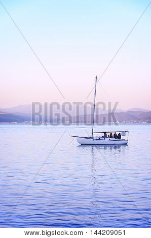 People enjoy the sunset on a sailboat in the ocean harbor in Wellington, New zealand