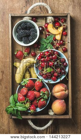 Summer fresh fruit and berry variety in rustic wooden tray over wooden backdrop, top view, vertical composition