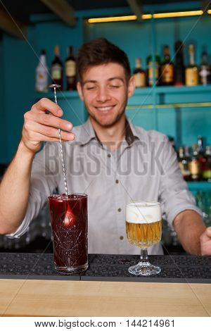 Barman in bar interior making alcohol berry cocktail. Professional bartender at work in bar mixing drink with ice in big glass and a beer portion stands near. Party time in night club