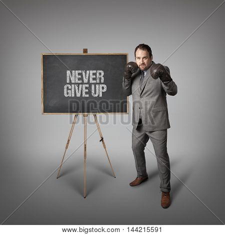 Never give up text on  blackboard with businessman wearing boxing gloves