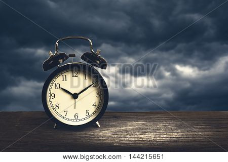 Alarm Clock On Wood With Blurry Rain Cloud In Background