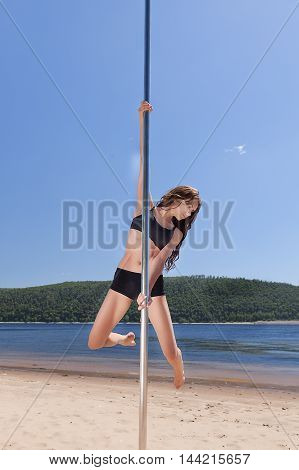 dancer on pole performs acrobatic summer beach