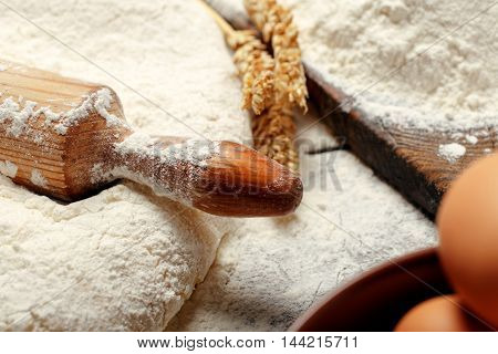 Rolling pin in the dough on wooden table close up in a bakery. Preparation of homemade bread