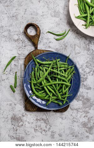 French bean in blue plate on old wooden board on the rough light surface top view