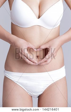 Beautiful slim waist of woman with heart isolated on gray background