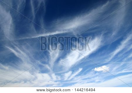 white cirrus clouds on the blue sky