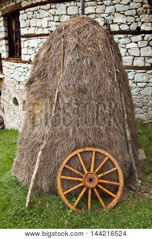haystack and wagon wheel in a farmyard