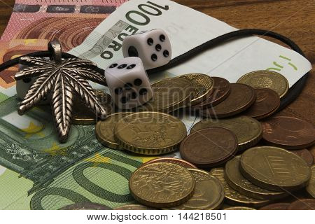 Suspension leaf of marijuana dice two coins euro banknotes on a wooden table