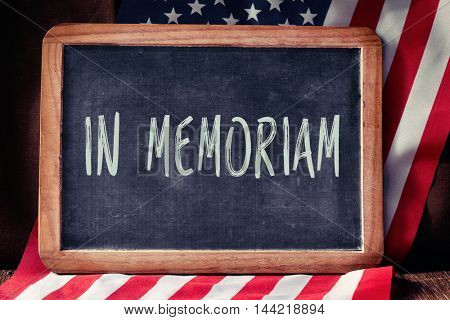 the text in memoriam, a latin phrase for in memory, written in a chalkboard and a flag of the United States, on a rustic wooden surface