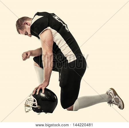 American football player, knelt on one knee, head bowed. Toned photo.
