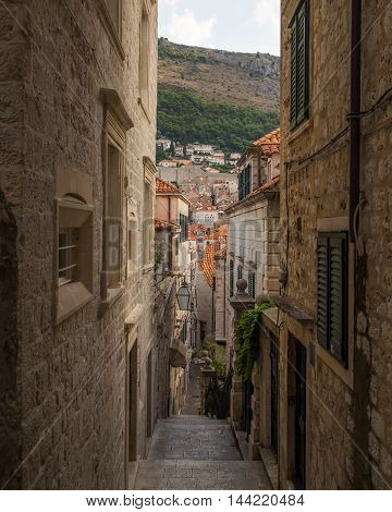 A view of along quiet streets in Dubrovnik during the morning. Lamps from shops can be seen.