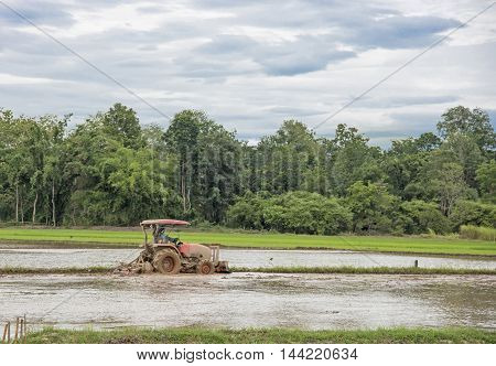 Thai farmer in heavy tractor during cultivation agriculture works at field with plough