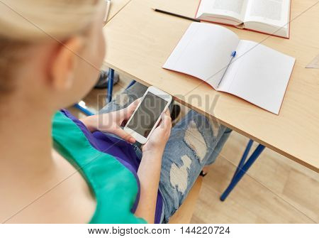 education, high school, learning, technology and people concept - student girl with smartphone texting on lesson