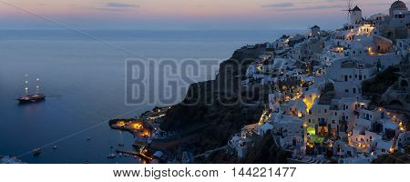 Romantic Evening in the Santorini with lights and boat