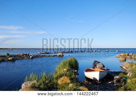 White small boat moored by the stony coast of the island Oland in the Baltic Sea