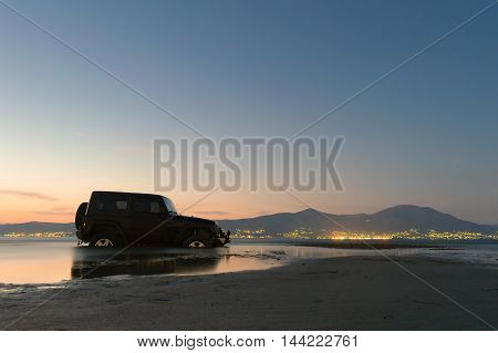 Athens, Greece 1 July 2016. Jeep 4x4 stuck in the mud at a wetland in Oropos city in Greece against the night dusk.
