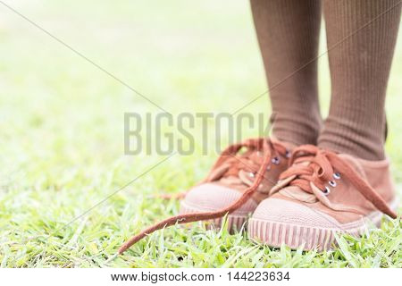Children foot resting on top of a soccer ball on green grass with copyspace soft focus