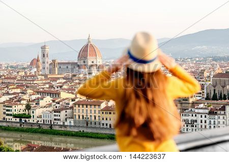 Young female tourist enjoying the view on the old town of Florence from Michelangelo square in the morning in Italy. Back focus