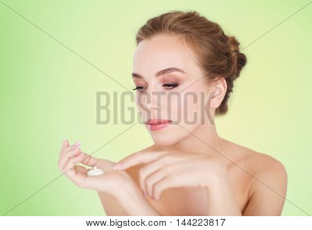 beauty, people, skincare and cosmetics concept - happy young woman with moisturizing cream on hand over green background