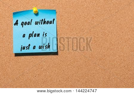 A goal without a plan is just a wish written by black marker on blue sticker pinned at notice board. Business, technology, internet concept. Stock Image.