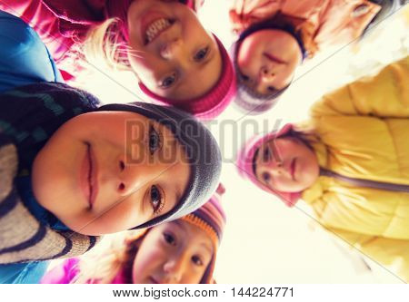 childhood, leisure, friendship and people concept - group of happy children faces in circle