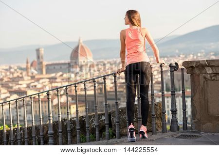 Young woman in sportswear enjoying great view on the old city background after morning exercise in Florence in Italy
