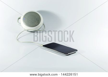 Plug the player device to the speakers and headphones on white background.