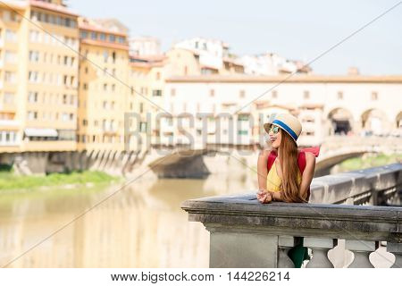 Young female traveler having fun flying with raised hands in front of the famous arch bridge in Florence