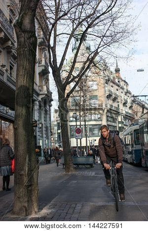 Zurich, Switzerland - November 27, 2011. A young man riding a bicycle on business.
