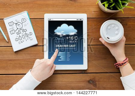 business, education, technology and people concept - close up of woman with weather forecast application on tablet pc computer screen, notebook and coffee on wooden table