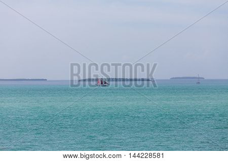 Huge sailboat with red sails on the blue seas off Key West