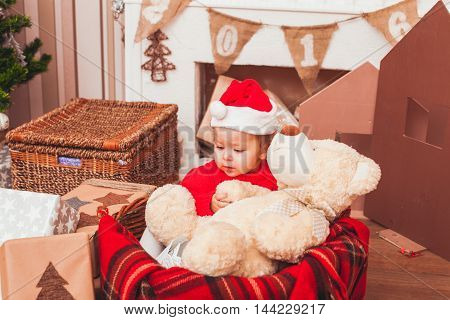 Happy pretty baby dressed in costume Santa Claus with Christmas gifts