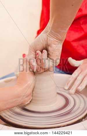 Hands of girl who tries to make pottery from white clay on a potter's wheel with teacher
