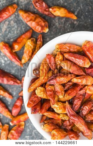 Dried mini chili peppers in bowl on kitchen table. Top view.