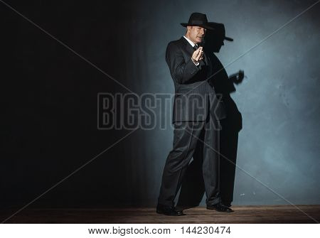 Film Noir Man Wearing Suit And Hat. Smoking Cigarette.