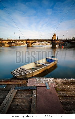 Amazing Sunrise View At Vltava River Bridge And Boat With Clear Water Reflection. Typical Prague Sun