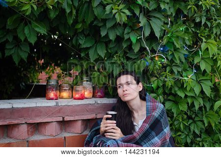 adult girl with cup on background of leaves