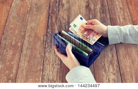 business, finance, saving, banking and people concept - close up of woman hands with wallet and euro money on wooden table