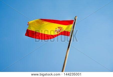 Spanish flag flying on a metal flag pole