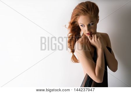 Portrait of beautiful red-haired woman presses her hands to face