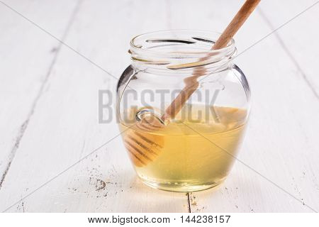 Jar Of Honey With Honeycomb On Wooden Table