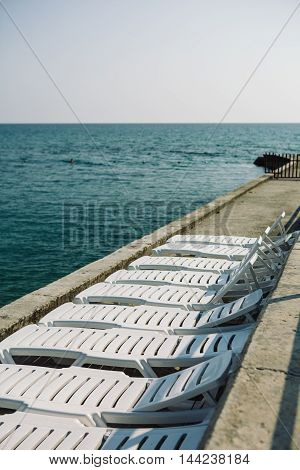 View of line of white deckchairs on cement coast against the sea.copy space