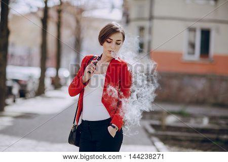 spectacular young brunette outside uses fashionable and healthy e-cigarette