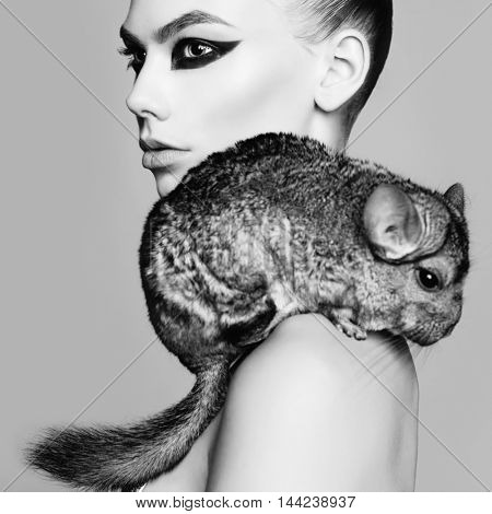 Glamour portrait of young beautiful woman with chinchilla
