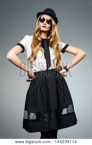 Fashion model posing. Beautiful young woman wearing pretty blouse and skirt. Studio portrait over gray background.