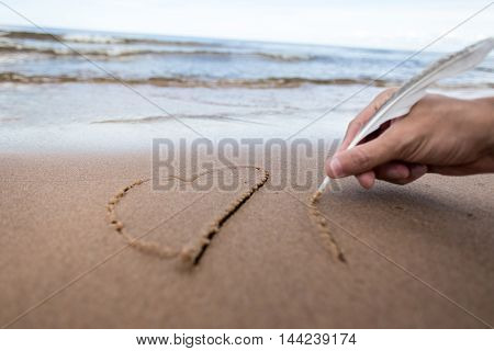 male hand writing on the sand with a feather